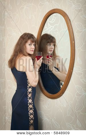 Beautiful Young Girl Standing Near A Mirror With Wine Glass In Hand