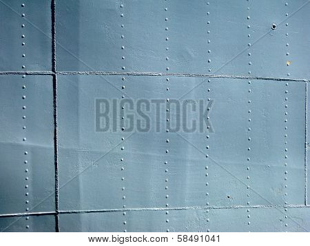 Detailed Gray Metal Historic Ship Wall With Seams And Rivets. With A Chip Of Paint.