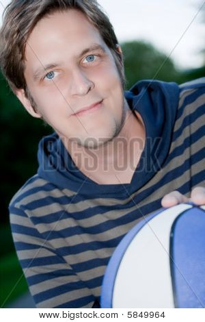Joven sonriente con el baloncesto
