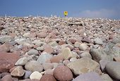 foto of lifeline  - Pink Pebbles and rocks beach of Mulrany in Ireland Europe on blue sky background with yellow lifeline - JPG