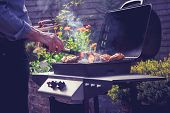 foto of braai  - Man is Cooking Meat On a Barbecue - JPG