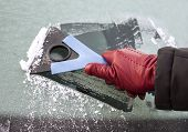 picture of ice-scraper  - Picture of a hand holding window scraper and removing ice of the car window
