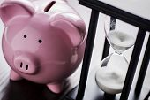 stock photo of pass-time  - Pink ceramic piggy bank with an hour glass conceptual of time running out to save for your retirement a nest egg or to meet your dreams - JPG