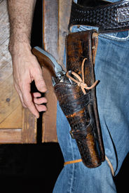 stock photo of wild west  - cowboy wearing a gun in his holster like the days of the wild west - JPG