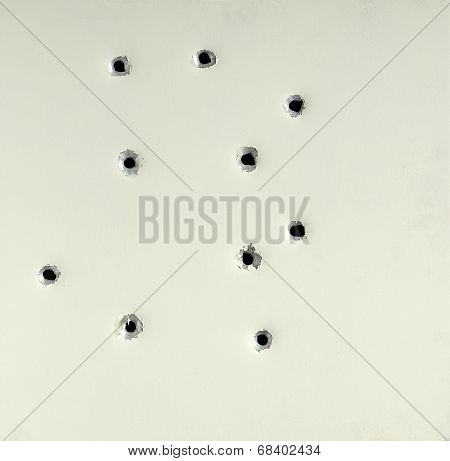 Bullet holes from  firearm in a metal plate