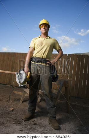 Construction Worker Standing With Saw