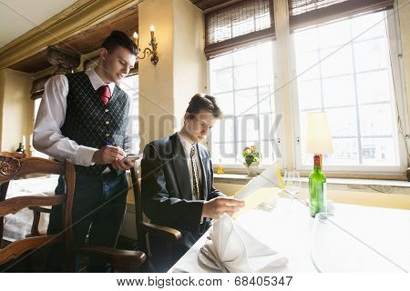 Waiter taking businessman's order at restaurant