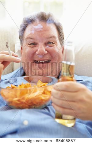 Overweight Man Eating Chips, Drinking Beer And Smoking