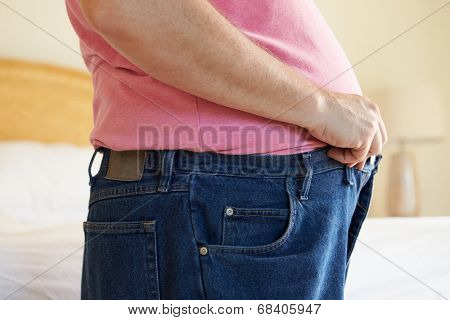 Close Up Of Overweight Man Trying To Fasten Trousers