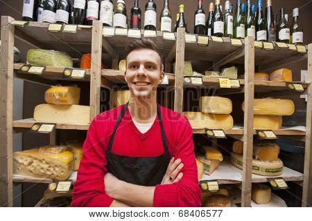 Happy male clerk standing against shelves in cheese shore