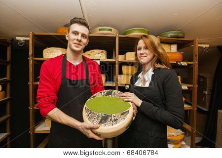 Portrait of confident salespeople showing cheese in shop