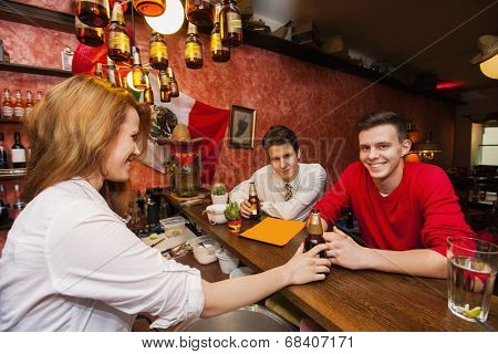 Female bartender serving beer to men at bar counter
