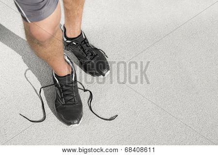 Low section of sporty man with untied shoelace standing on street