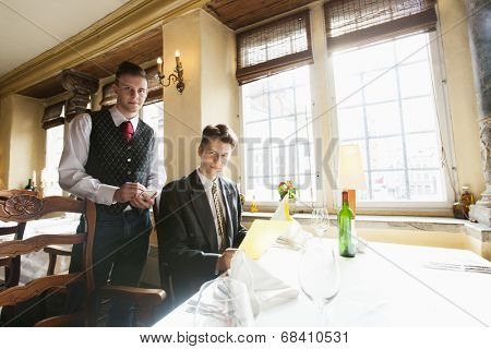 Portrait of waiter and businessman at restaurant table