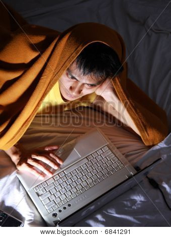 Man in blanket using laptop on bed