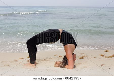 Woman in a Setu Bandha Sirsasana yoga pose