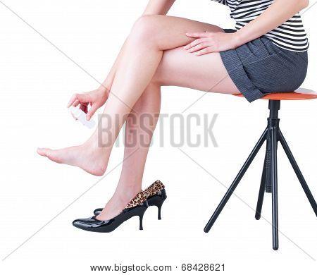 woman using a foot deodorant spray