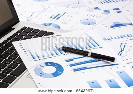 Laptop And Pen With Blue Business Charts, Graphs, Statistic And Documents