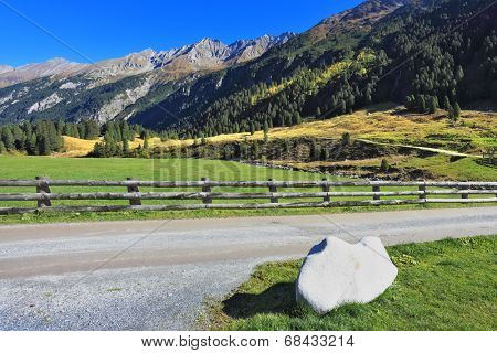 Rough stream, dense coniferous forest and easy farmer fence. Picturesque mountain valley