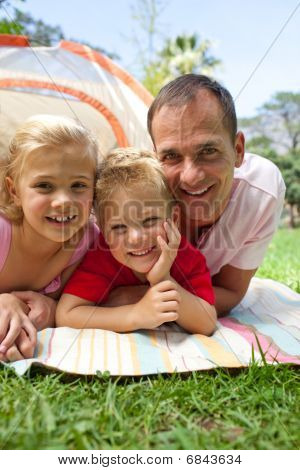 Happy Father And His Children Lying On The Grass