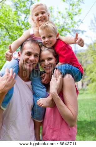 Smiling Parents Giving Their Children Piggy-back Ride