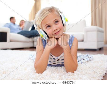 Adorable Little Girl Listening Music Lying On The Floor