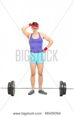Full length portrait of a doubtful male athlete standing behind a barbell isolated on white background