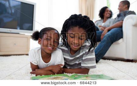 Hermanos lindos leyendo tirada en el suelo