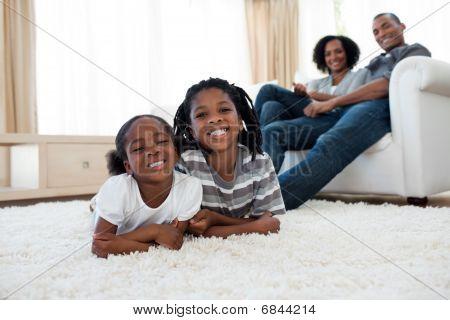 Bruder und Schwester auf dem Boden liegend lächelnd