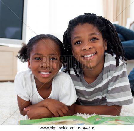 Close-up Of Siblings Reading