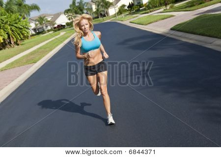 Beautiful Blond Woman Running In Suburban Street