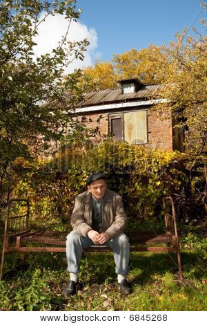 Serious middleaged man sit on old rusty bed in autumnal garden