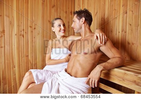 Happy couple sitting together in hotel sauna in their holidays