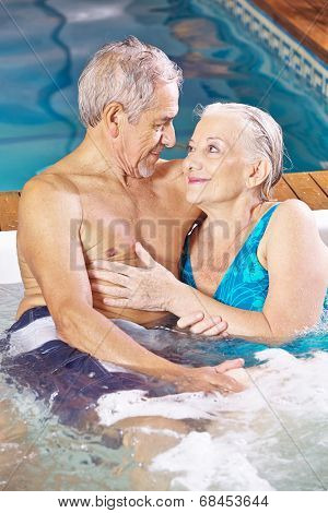 Happy senior couple relaxing in a spa hotel whirlpool