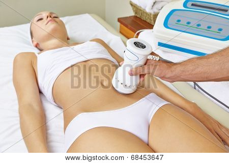 Woman receiving electric massage on stomach for muscle training in spa