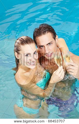 Happy couple drinking glass of sparkling wine in hotel pool