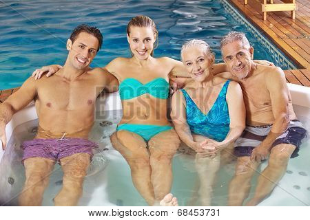 Happy family with senior couple relaxing in a hotel whirlpool