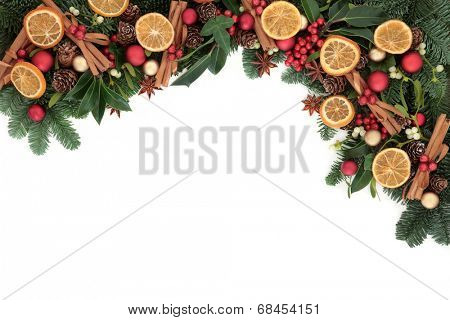 Christmas background border with cinnamon spice, dried orange fruit, bauble decorations, holly and winter greenery over white with copy space.