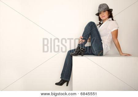 Girl in jeans hat and white shirt sitting in white studio. Horizontal format.