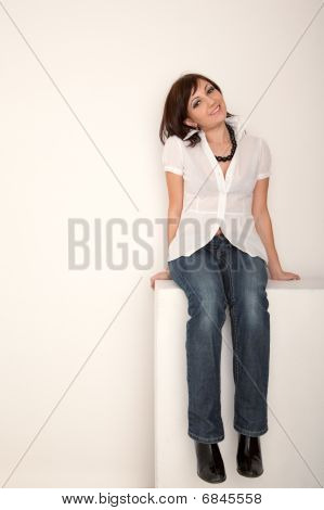 Smiling girl in jeans and white shirt sitting in white studio. Vertical format.