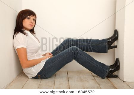 Portrait of pensive girl in jeans and white shirt sitting in white studio.