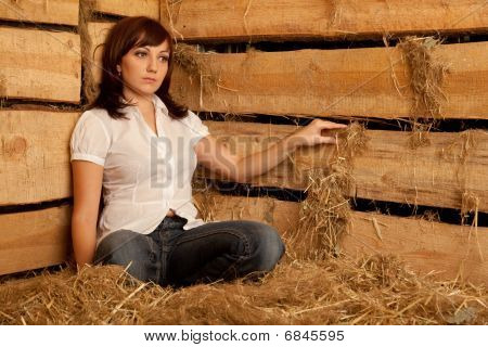 Portrait of girl in white shirt and blue jeans sitting on pile of straw in hayloft.