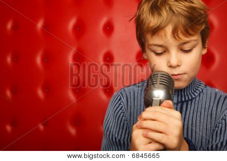 Portrait Of Boy With Microphone On Rack Against Red Wall. Ð¡lose Up. Horizontal Format.