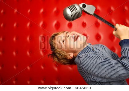 Singing boy with microphone on rack against red wall. Horizontal format.