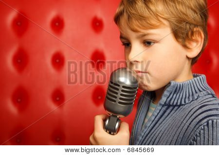 Sad boy with microphone on rack against red wall. Close up. Horizontal format.