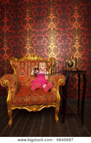 Little girl in red dress talking vintage phone. Interior in retro style. Against ornamental wallpape