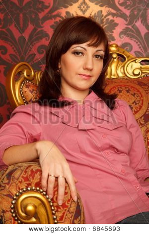 Portrait of girl sitting in armchair. Interior in retro style. Close up. Vertical format.