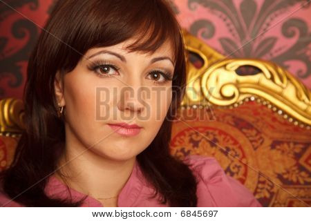 Portrait of girl in red shirt sitting in armchair. Interior in retro style. Close up.