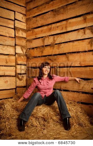 Portrait of girl in red shirt sitting on pile of straw in hayloft against the wall of boards