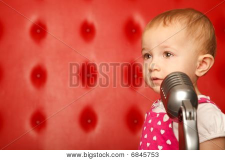 Portrait of little girl with microphone on rack against red wall. Looking aside.